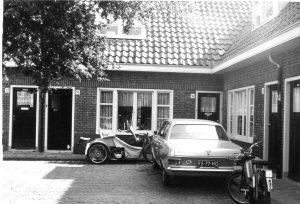 De invalide mw. Sloos weigert de huurverhoging te betalen vanwege de slechte toestand van haar woning aan de Transvaalhof. Pas als zij door de vloer zakt wordt er gerepareerd. Op de foto: Transvaalhof 31 met de invalidenwagen van mw. Sloos 31 mei 1975